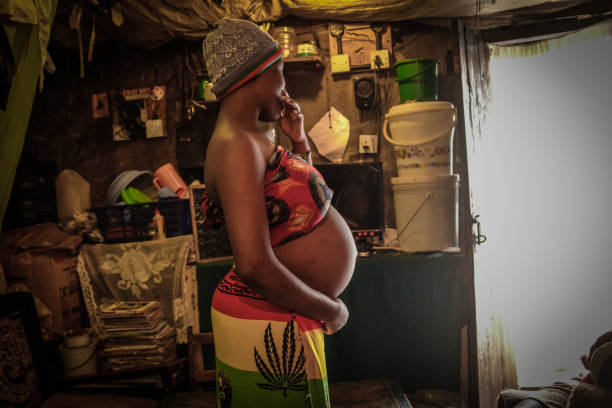 NAIROBI, KENYA - 2020/06/25: 18 year old Viela Akinyi is seen holding her baby bump inside her home in Kibera Slums. Some research indicates that up to a third of more of girls aged between 15-22 living in Nairobis main slums experience an unwanted pregnancy. (Photo by Donwilson Odhiambo/SOPA Images/LightRocket via Getty Images)